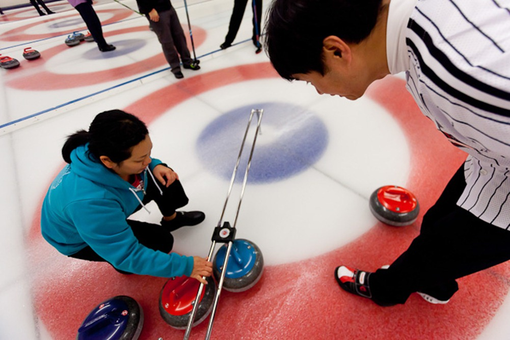 Measuring her stone, Kris Ikegami of Team Schreiber confirms red is shot rock while Thomas Brandt of Team Gale-Seixeiro observes at the Granite Curling Club in Seattle on Monday, Jan. 9, 2012 during round one of Monday League playoffs. Founded in 1961 the Granite Curling Club is home to more national champions than any other curling club in the United States. (Photo/Neil Enns)