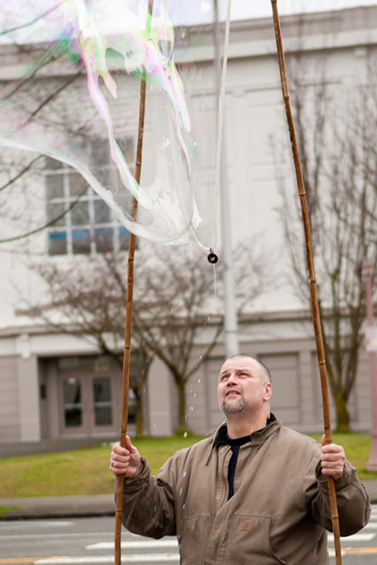 "Watching his bubble, Eddie Blunt brightens a dreary day in Everett, WA, on Sunday, Jan. 22, 2012. Blunt's favourite location to practice his craft is outside Providence Children's Center in downtown Everett, which he says gives him ""the most bang"" for each bubble. (Photo/Neil Enns)"