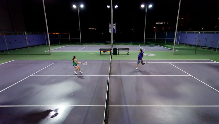 Crashing the net, Vicky Tran, left, and Kevin Huynh, right, play tennis under the lights at the University of Washington in Seattle, WA, on Thursday, Jan. 26, 2012. The cousins say they were craving tennis after growing up playing the game daily in their hometown of Kent, WA. (Photo/Neil Enns).