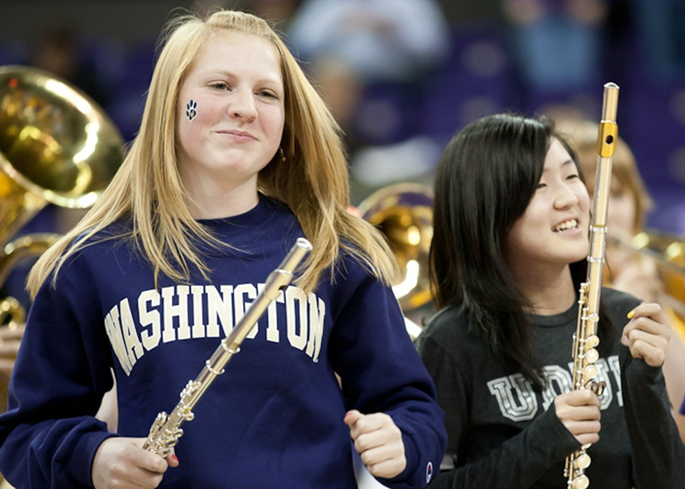 Dancing during a song, 14-year-old Caryln Beaudry, left, and 13-year-old Jubilee Cho, right, perform with the Whitman Middle School Grade 8 band during halftime at the University of Washington Husky Women's basketball game in Seattle, WA, on Thursday, Jan. 26, 2012. The Husky Women beat the Arizona Wildcats 77-48. (Photo/Neil Enns)