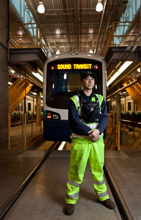 Electromechanic Calvin Lee stands in front of one of the trains maintains at the service facility in Seattle, WA on Tuesday, March 6, 2012. Lee has worked at SoundTransit since it started operating 3 years ago. (Photo/Neil Enns)